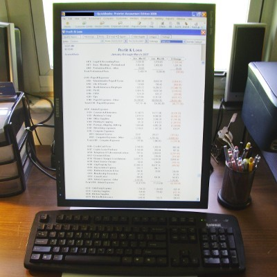 Computer Displaying a Financial Report Along With a Printed Charts and Figures
